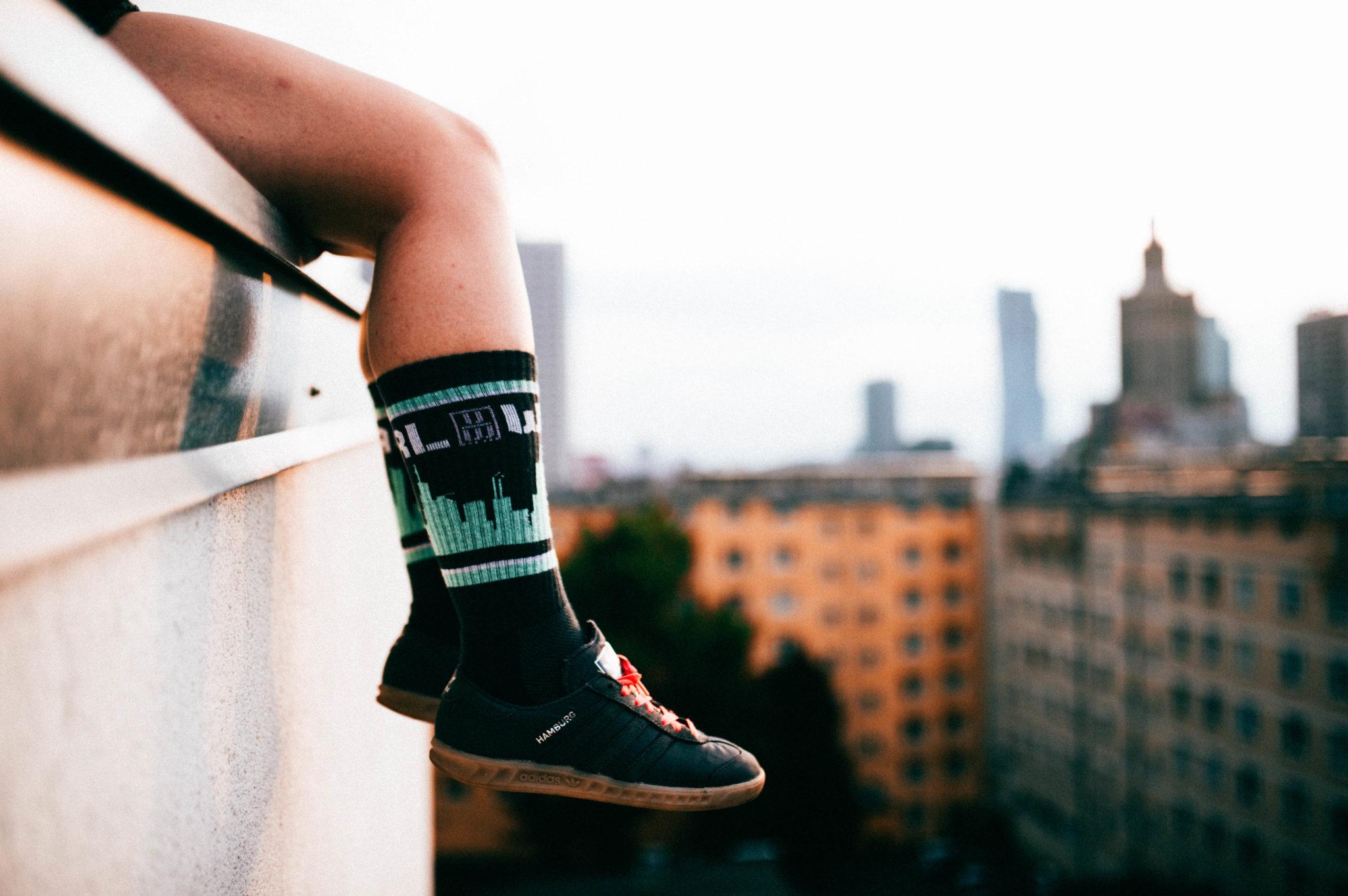 Nogi zwisające ze szczytu budynku, ze skarpetkami w warszawski motyw