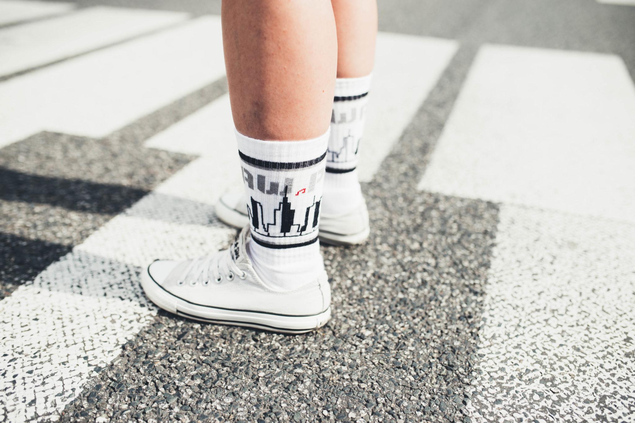 Nogi w białych butach i skarpetkach z motywem Warszawy