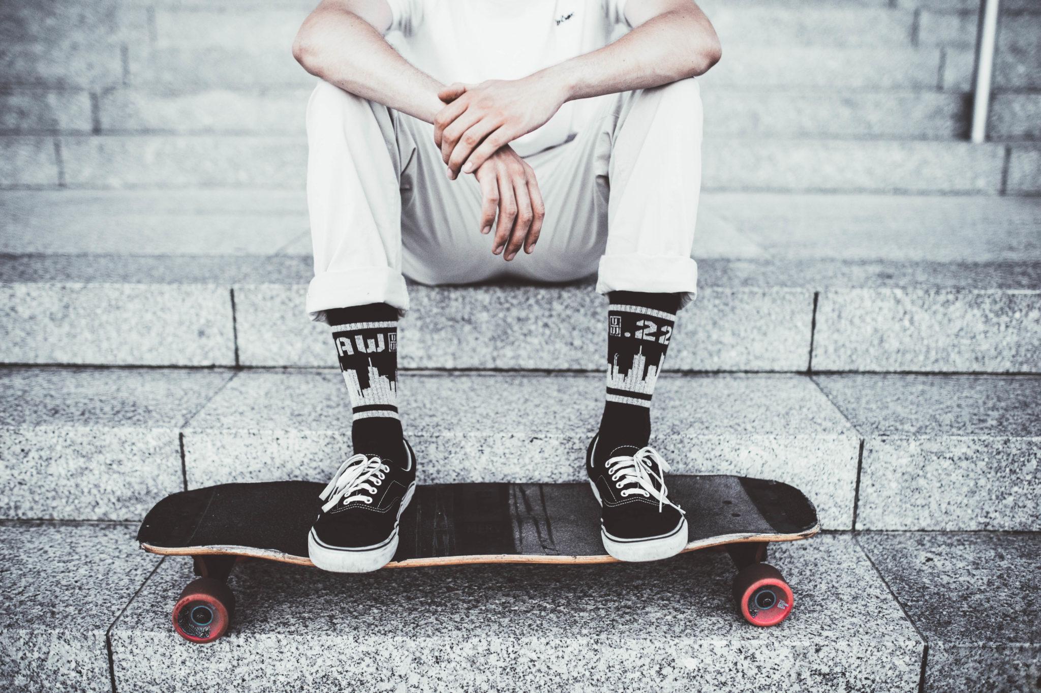 Chłopak opierający nogi na deskorolce w czarnych trampkach i skrapetkach z motywem Warszawy