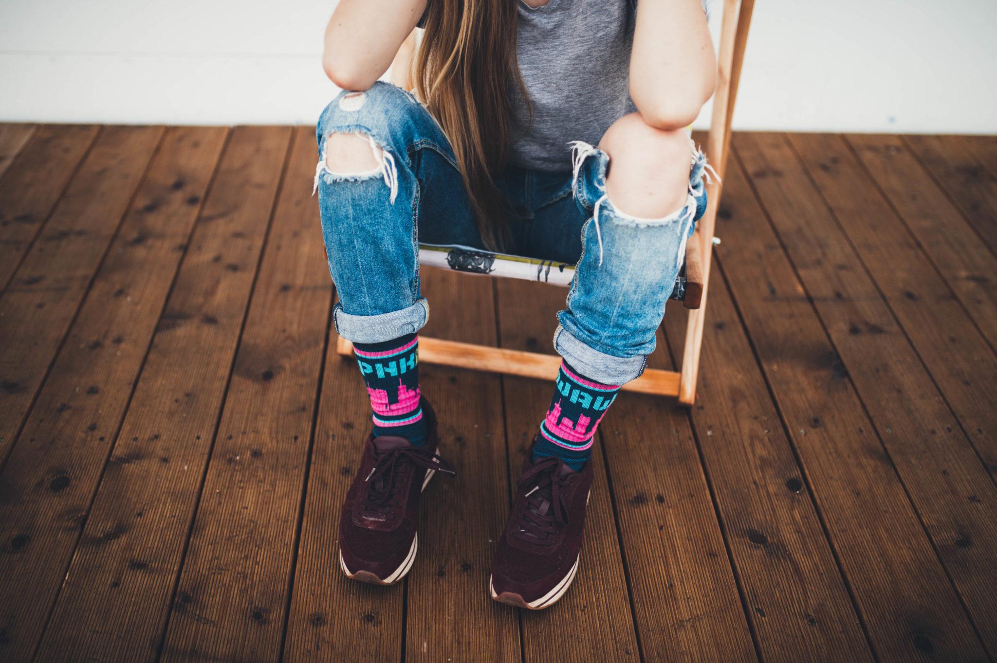 Dziewczyna siedząca na leżakju w podziurawionych jeansach, czarnych butach i skarpetkach z motywem Warszawy