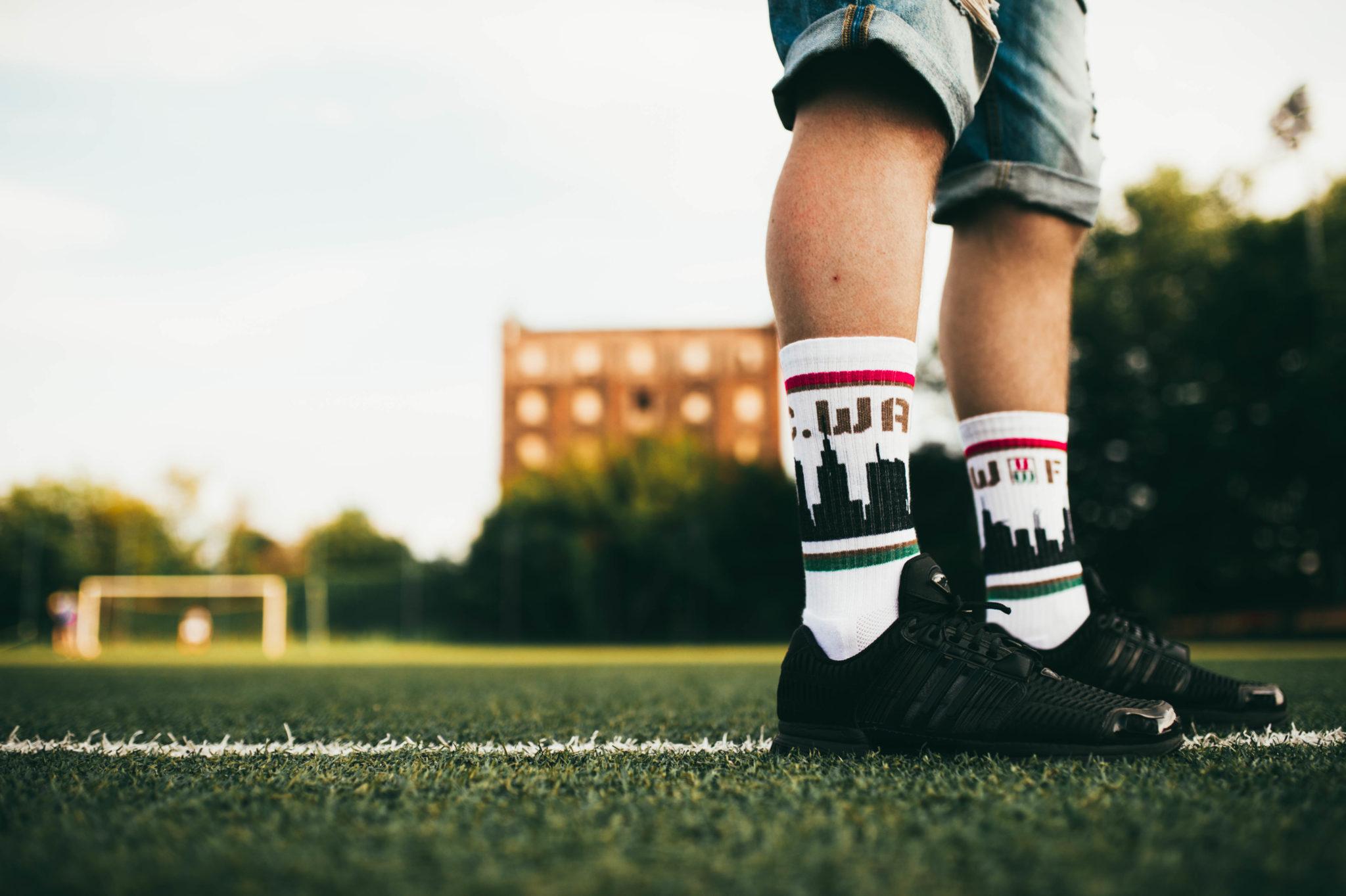 Męskie nogi na boisku ze skarpetkami z motywem Warszawy
