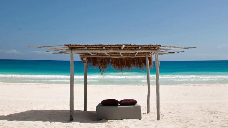Leżak stojący pod babmusowym daszkiem na piaszczystej plaży