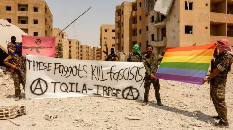 Zdjecie żołnierzy-ochotników, ktorzy trzymaja flagi srodowiska LQBT oraz transparent z haslem these faggots kil facists. W tle widac miasteczko Syrii, ktore jest dotkniete wojną i zniszczeniem.