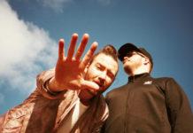 Ujęcie z dołu twarzy dwóch mężczyzn, jeden ma koczek na głowie i trzyma dłoń przed obiektywem, drugi patrzy w bok, ma czarną bluże, okulary i czapkę