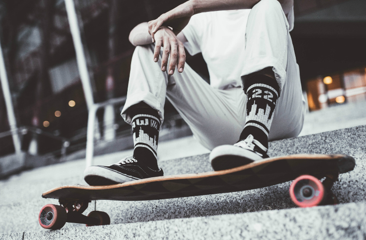 Ujęcie nóg chłopaka w skarpetkach z motywem Warszawy, opierającego nogi na deskorolce