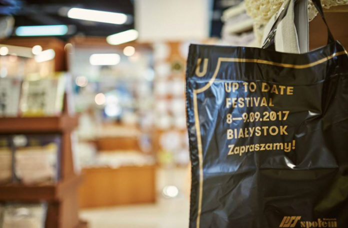 Czarna reklamówka ze złotymi elementami zapowiadająca festiwal Up To Date