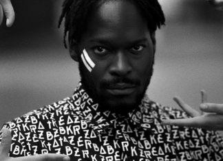 Czarno-białe zdjęcie przedstawiające czarnoskórego mężczyzne w koszuli z literami i dwoma białymi paskami na policzku
