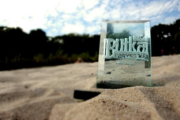 Szklana bryła z napisem Bułka Paryssska stojąca na piasku