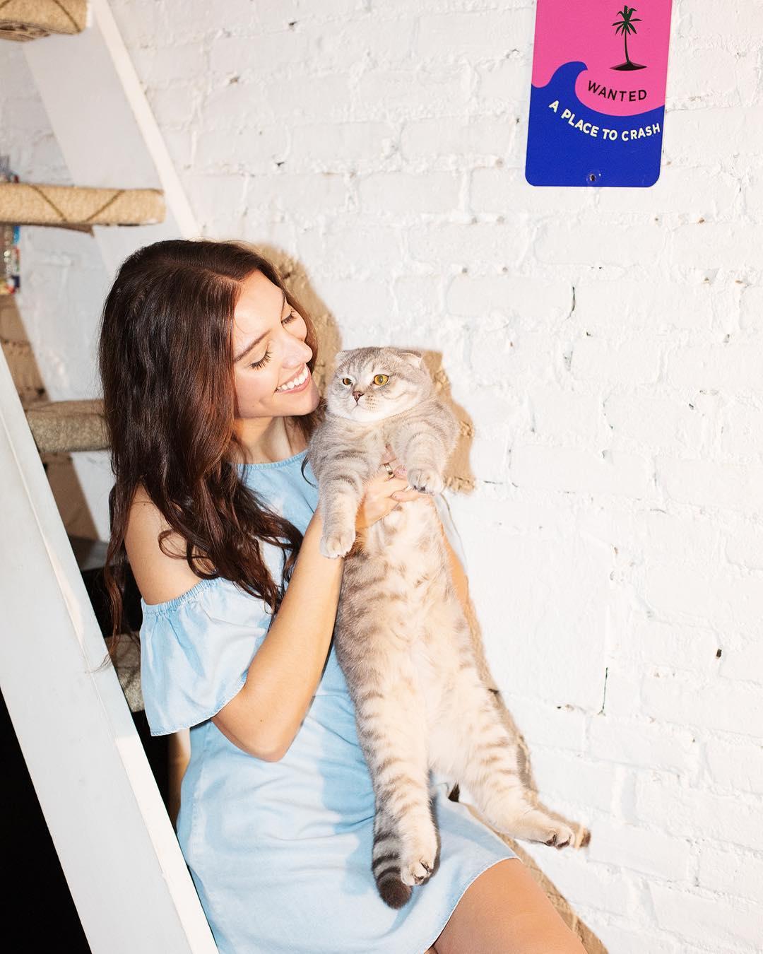 Kobieta opierająca sie o schody, trzymająca na rękach kota
