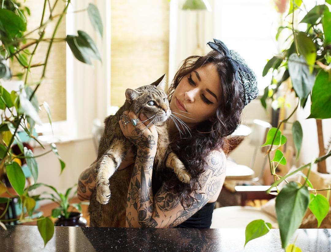 Dziewczyna w bandanie na głowie trzymająca na rękach kota