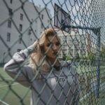 Dziewczyna stojąca na boisku odgrodzonym siatką, ubrana w szarą bluzę