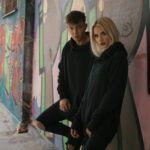 Chłopak i dziewczyna ubrani na czarno, opierający się o ścianę z graffiti