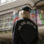 Dziewczyna na tle graffiti odwrócona tyłem w czarnej kurtce z napisem The Girl Next Door