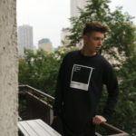 Chłopak w czarnej bluzie opierający się o balustradę balkonu