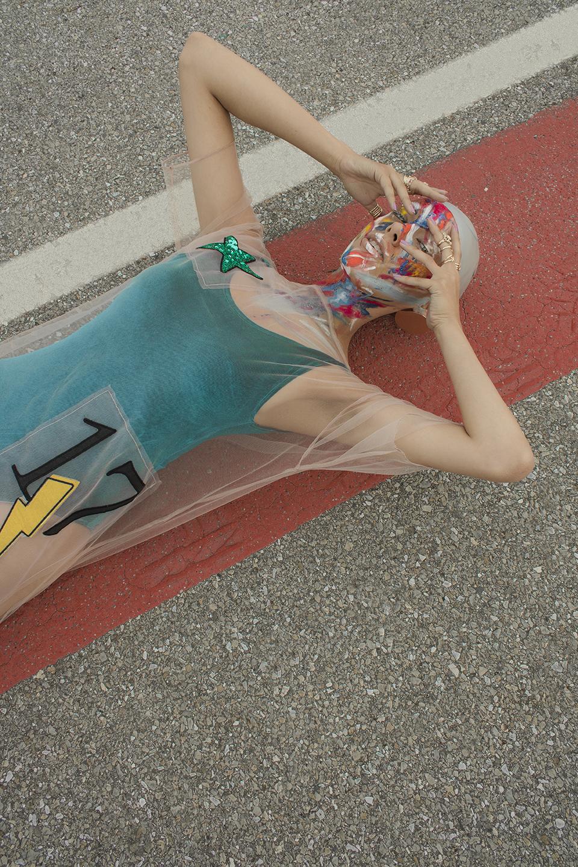 Dziewczyna leżaca na ziemi w niebieskim kostiumie kąpielowym z numerem 17, zasłaniająca twarz rękami