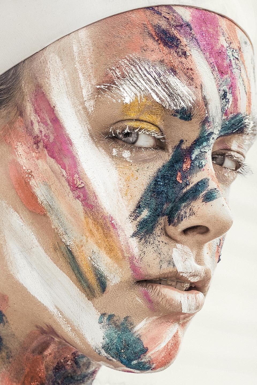 Portret dziewczyny z pomalowaną różnymi kolorami farb twarzą