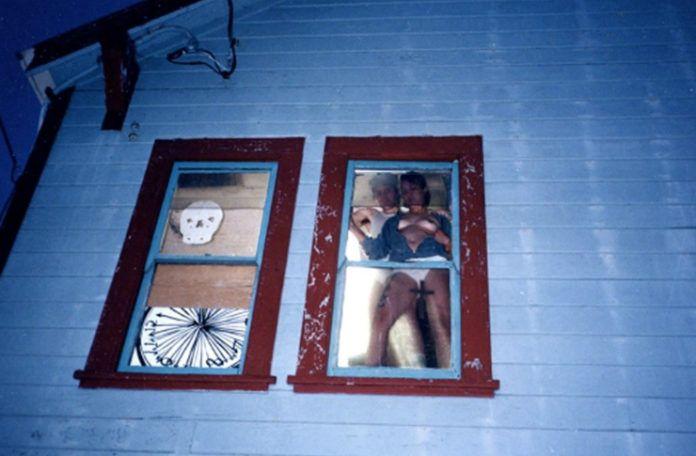 Zdjecie robione nocą. Widać na nim parę uprawiająca seks w oknie. Kobieta przylega do szyby. Pomiędzy nogami trzyma krzyż. Mężczyzna jest za nią. Widać białe ściany domu.