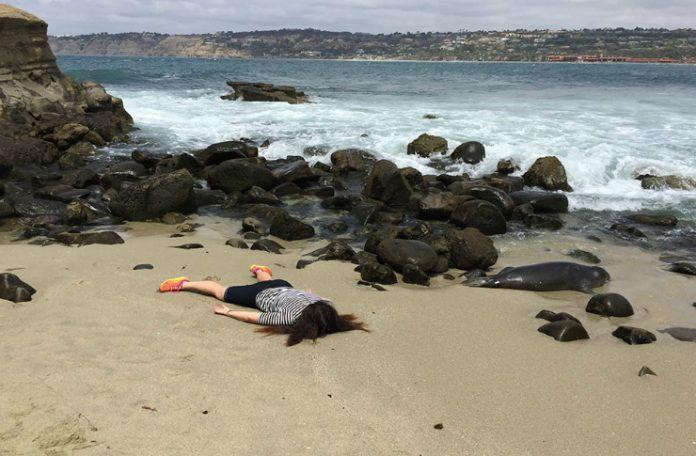 Dziewczyna leżąca twarzą do ziemi nad brzegiem plaży