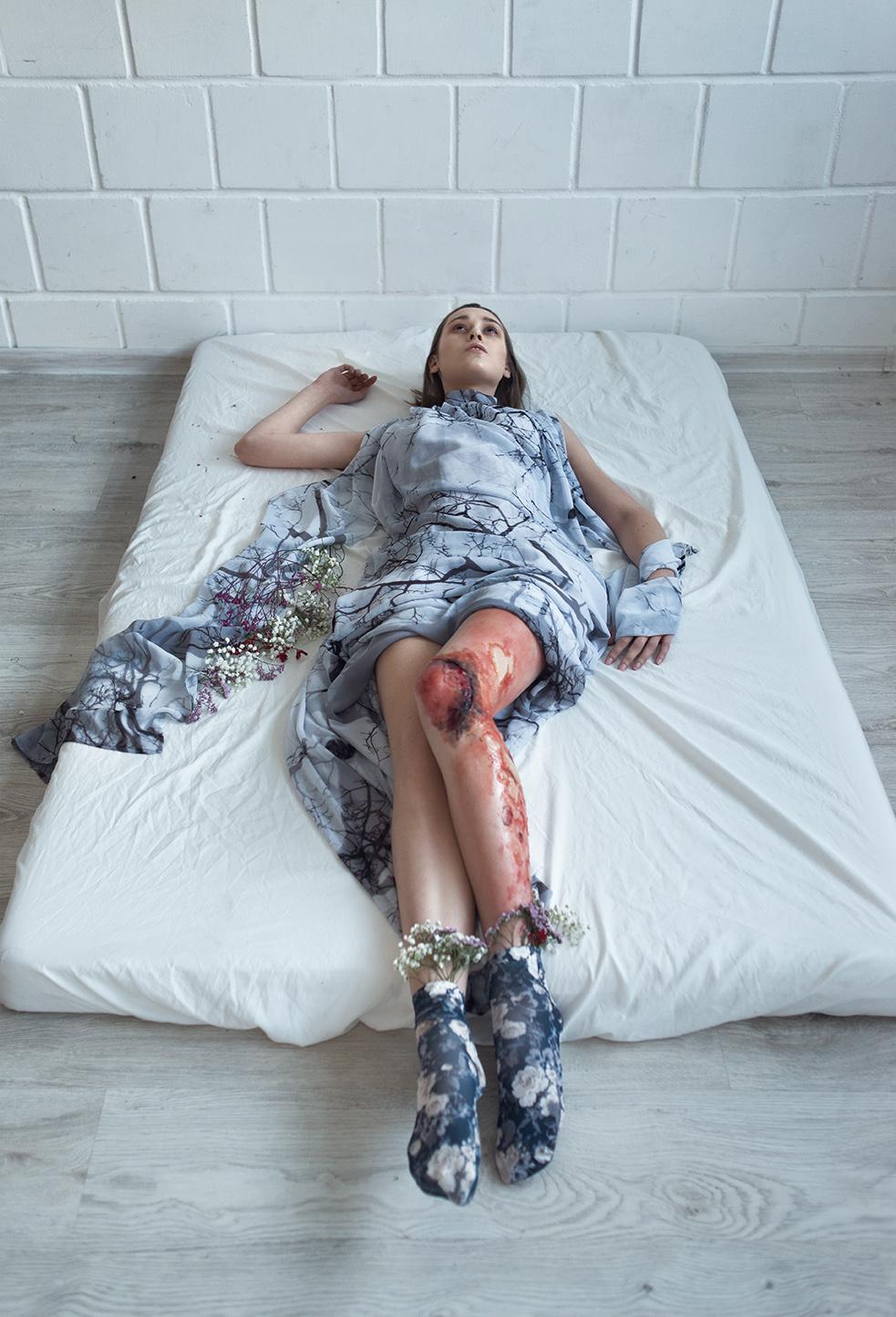 Leżąca na materacu kobieta ubrana w błękitną sukienkę, z zakrawioną nogą