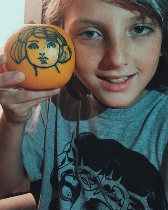 Zdjęcie chłopca trzymającego w dłoni pomarańcz z wytatuowaną twarzą kobiety