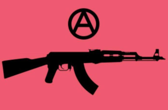 Logo organizacji TQILA, ktora broni srodowisk LGBT w Syrii i na bliskim wschodzie. Czarny maszynowy karabin AK47 na rozowym tle. Nad nim umieszczone w kółku A.