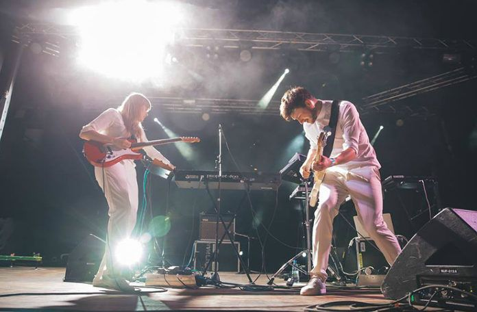 Kobieta i mężczyzna stojący na scenie grający na gitarach, ubrani na biało