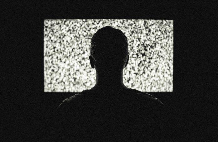 Człowiek w ciemnym pomieszczeniu siedzący przed włączonym, śnieżącym telewizorem