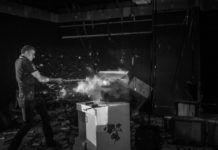 Czarno-białe zdjęcie na którym mężczyzna rozwala jakieś sprzęty kijem beseballowym