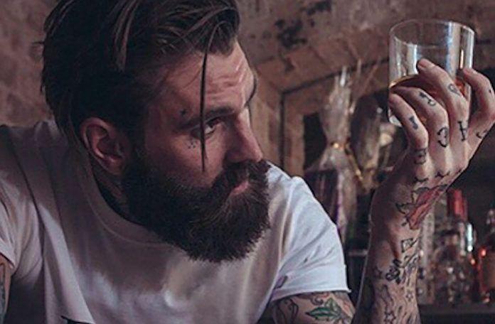 Mężczyzna z brodą trzymający w dłoni szklankę