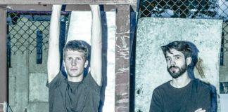 Dwóch mężczyzn - jeden blondyn trzymający rękami drewnianą belkę, drugi brunek z zarostem