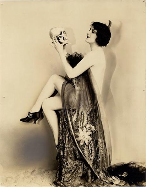 Prawie naga kobieta trzyma czaszkę.