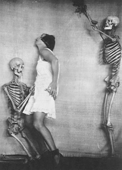 Kobieta stojąca obok szkieletu, za nią drugi szkielet