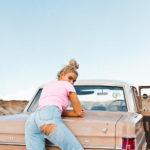 Dziewczyna w jeansach z dziurą na pośladku, oparta o tył różowego samochodu