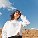 Dziewczyna w białej bluzie stojąca na tle błękitnego nieba