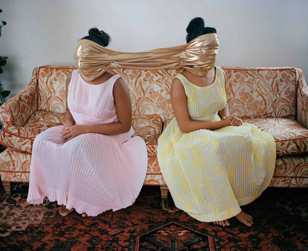 Dwie kobiety siedzące w sukienkach na kanapie z zakrytymi jedną chustą twarzami