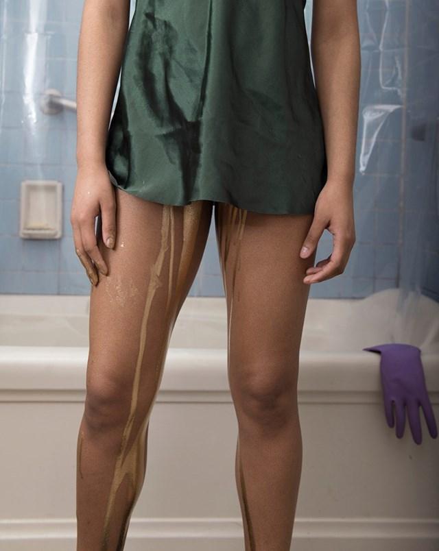 Nogi kobiety z między których wycieka złoty płyn