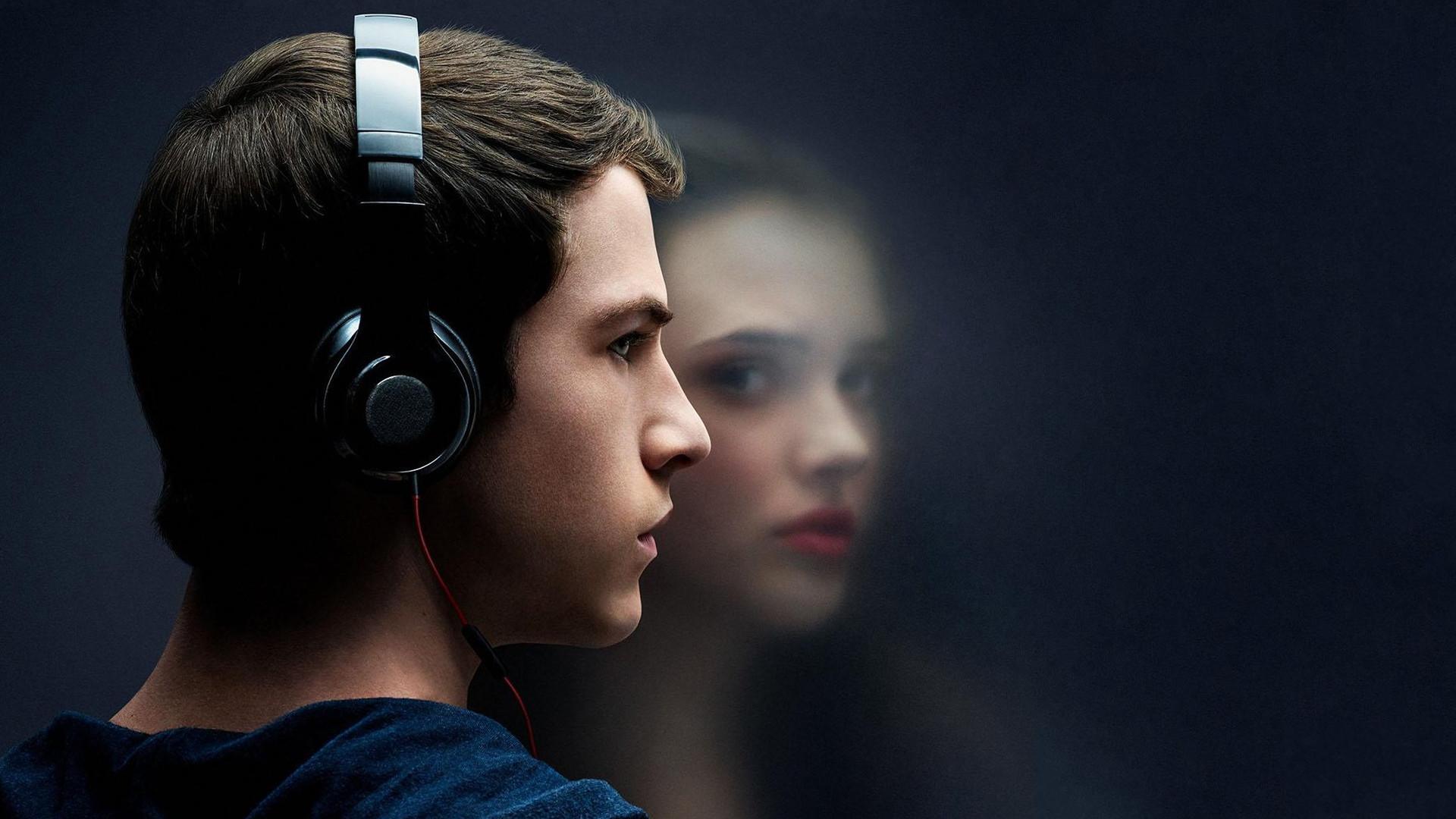 Chłopiec w słuchawkach stoi naprzeciwko rozmazanego odbicia dziewczyny.