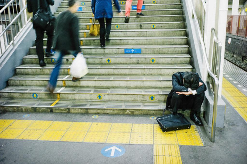 biznesmen śpiący na siedząco na schodach metra