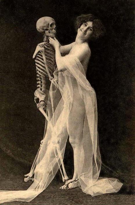 Kobieta w przezroczystej sukni obejmuje kościotrupa.