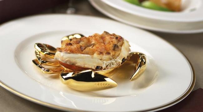 Krab podany na talerzu ze złotymi szczypcami