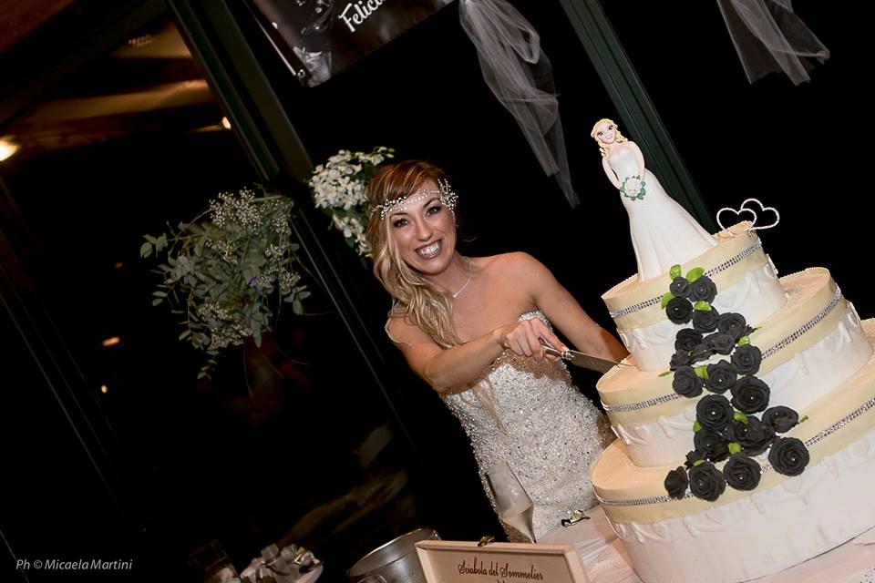 Dziewczyna w sukni ślubej krojąca tort