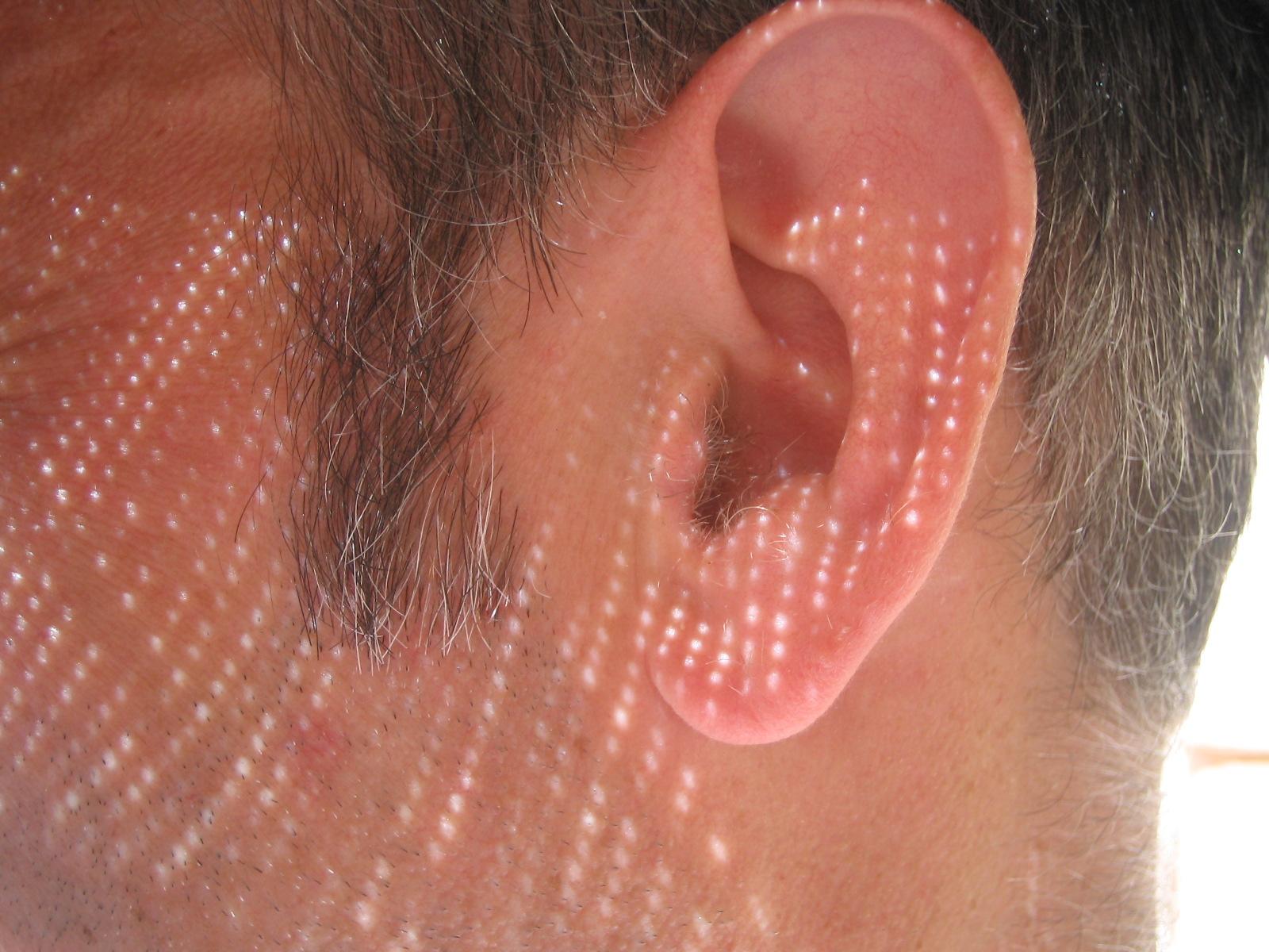 Zbliżenie męskiego ucha, widać też fragment włosów