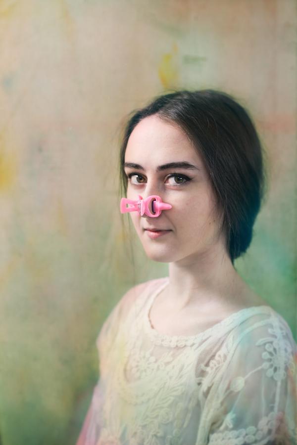 Portret dziewczyny w białej sukience z dziwnym, różowym klipsem na nosie