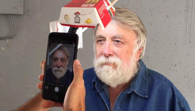 Ręka robiąca zdjęcie iPhonem staremu mężczyźnie.