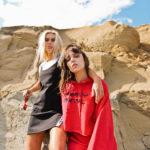 Dwie dziewczyny, jedna ubrana w czarną sukienkę, druga w czerwoną bluzę, stoją na tle piaskowych skał