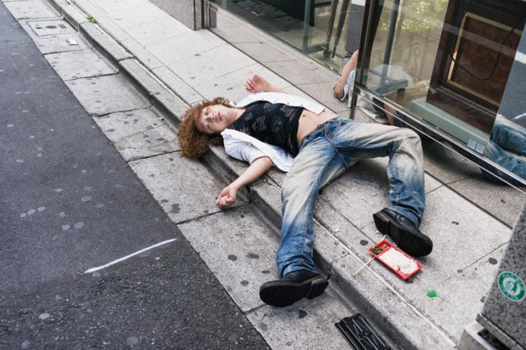 pijany japończyk śpiący na chodniku