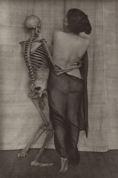 Półnaga kobieta pozująca ze szkieletem