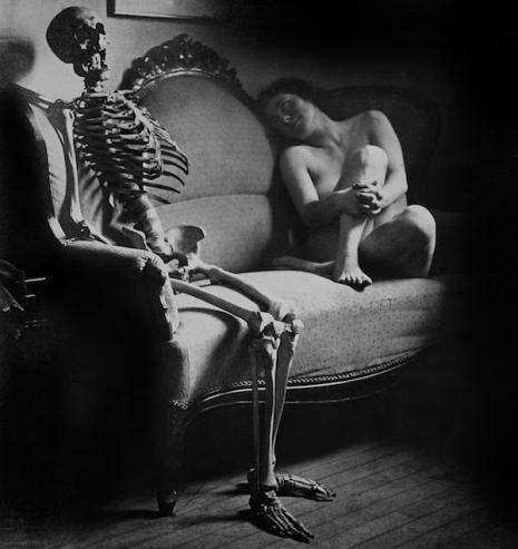 Naga kobieta siedząca a kanapie obok szkieletu