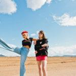 Dwie dwiewczyny: jedna w jeansowych spodniach z jedną nogą w górze, czarnym tshircie i czerwonym berecie, druga w czerwonych spodenkach i czarnej bluzie