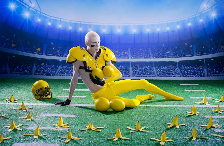 mężczyzna przebrany za banana na boisku obłożony skórkami dookoła
